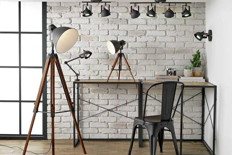 An industrial style home office with a floor lamp, table lamps and spotlights.