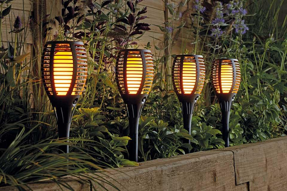 Four Argos Home solar dancing flame torches in a garden at night-time.