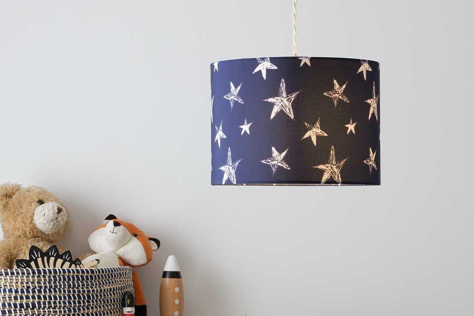 A star print lampshade in a children's bedroom with a teepee in the background.