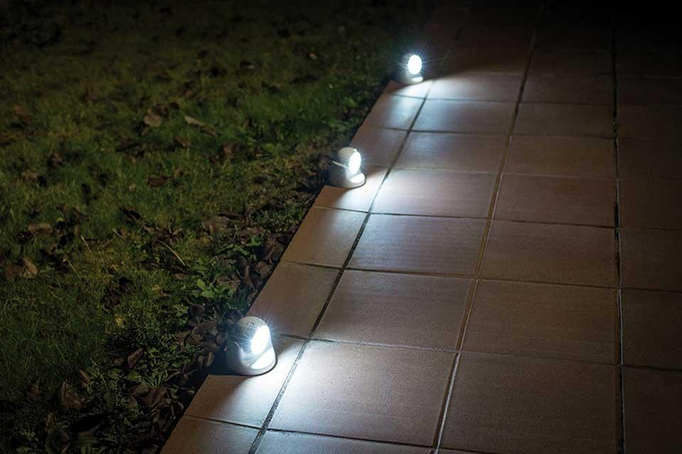 The Vigilamp LED sensor lights lit up at night-time on a pathway.