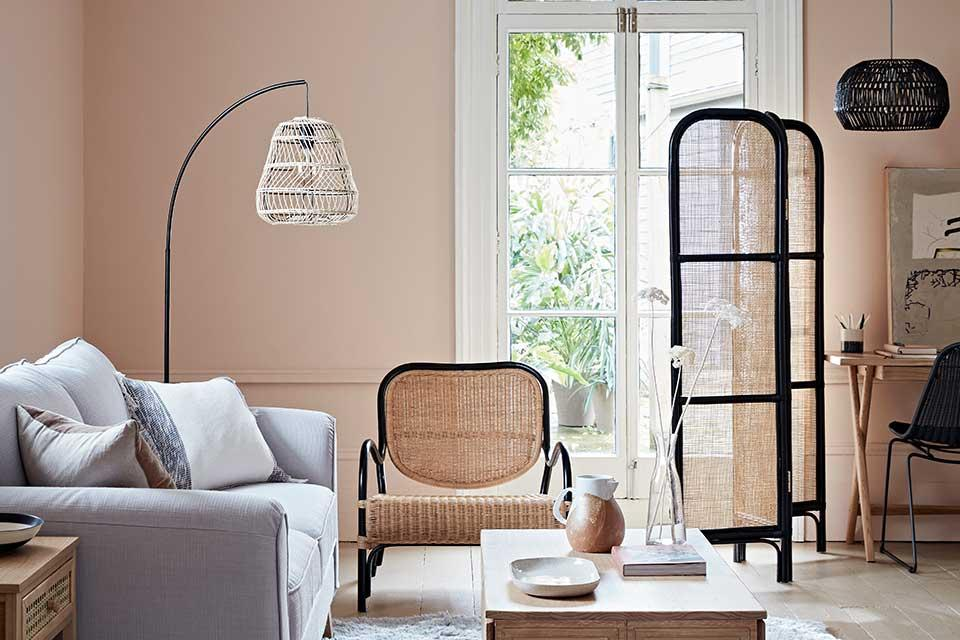 The Argos Home rattan floor lamp in a lounge with a grey sofa and rattan chair and screen.