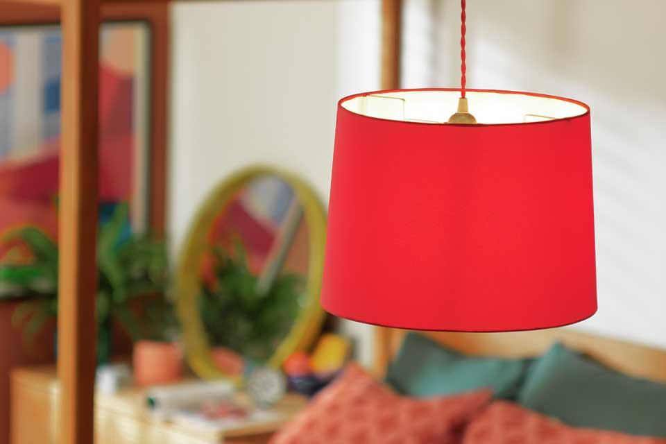 The Argos Home large red 35cm lampshade above a four-poster bed.