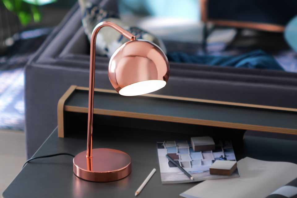A copper table lamp sitting on a desk with some homework next to it.