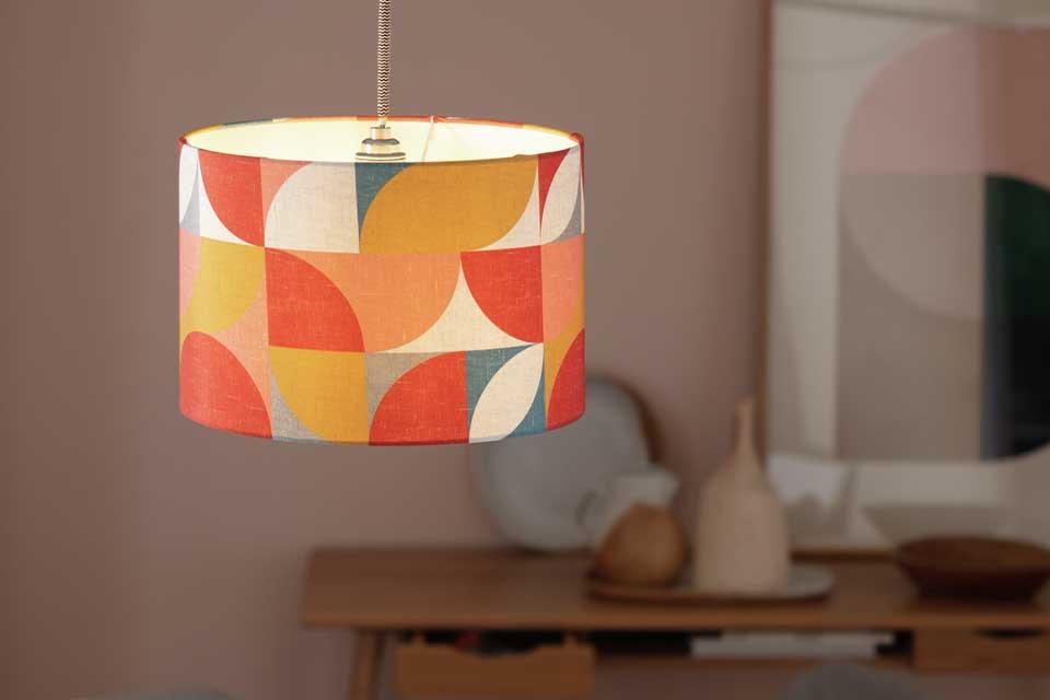 The Argos Home orange and red geometric printed lampshade above a glass dining table.