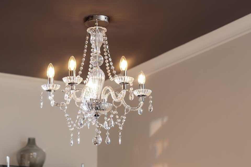 The Argos Home Como glass chandelier above a black dining table.