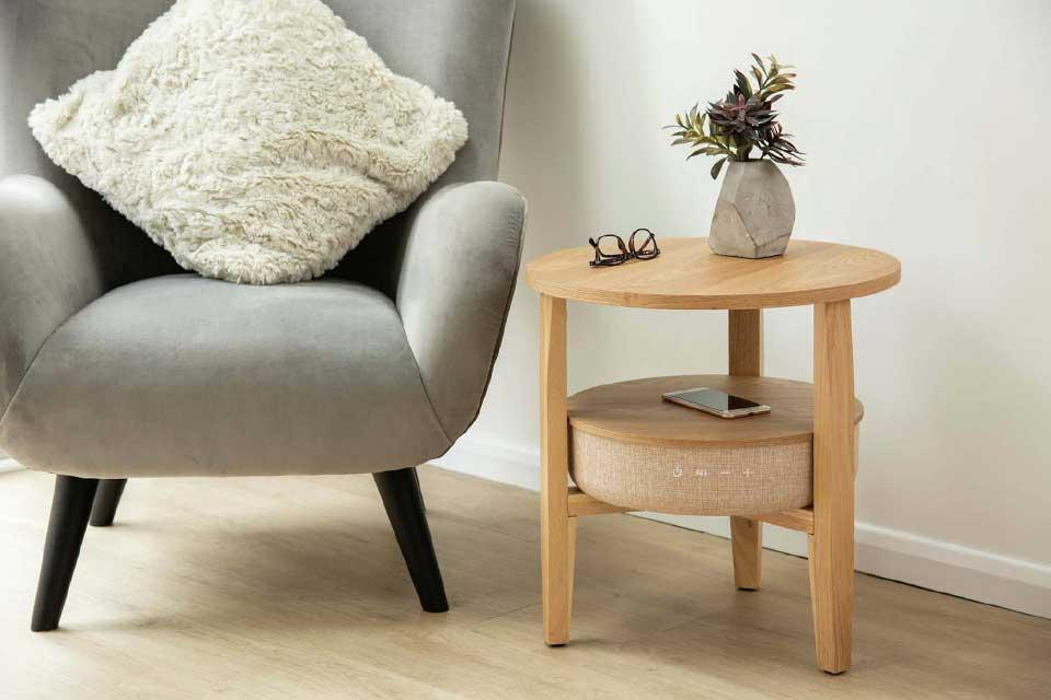 Koble wireless charging Bluetooth side table in oak-effect with a charging mobile phone on it.