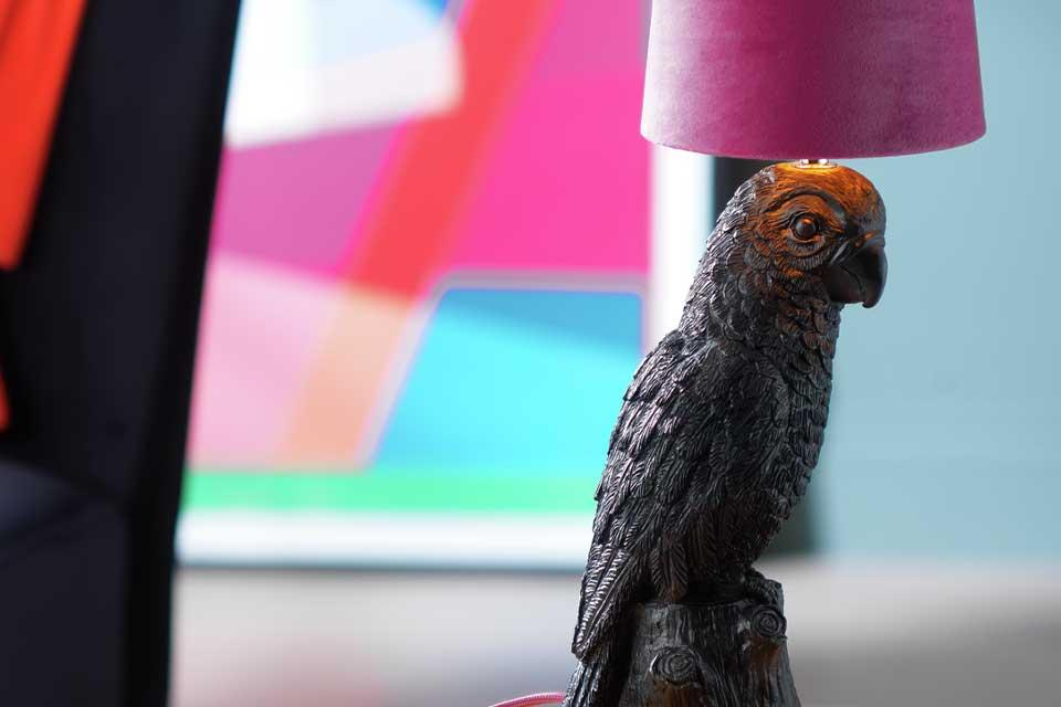 A flocked parrot table lamp with bright pink shade.