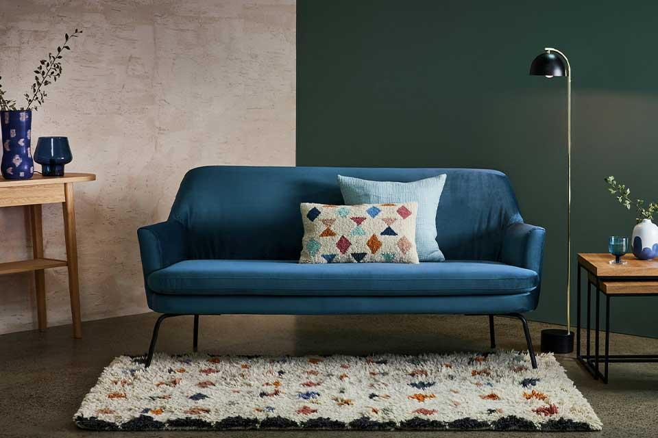 A blue velvet Habitat sofa with a geometric rug in front.