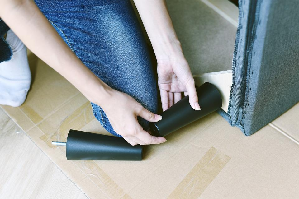 A woman attaching a plastic leg to a sofa.