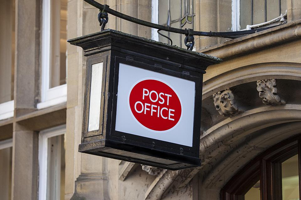 A post office sign outside a building.