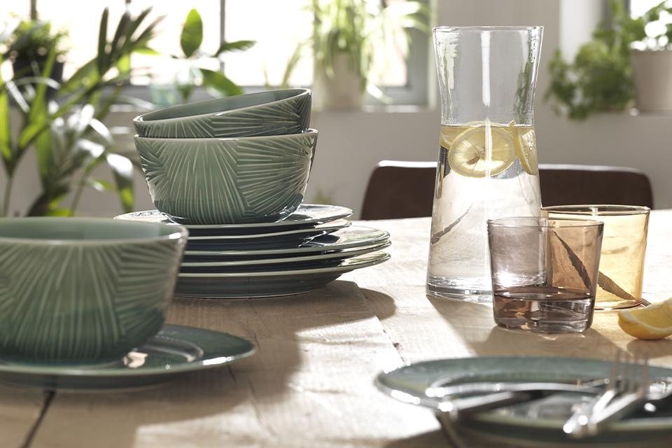 Textured green tableware and glassware on a rustic wooden dining table.