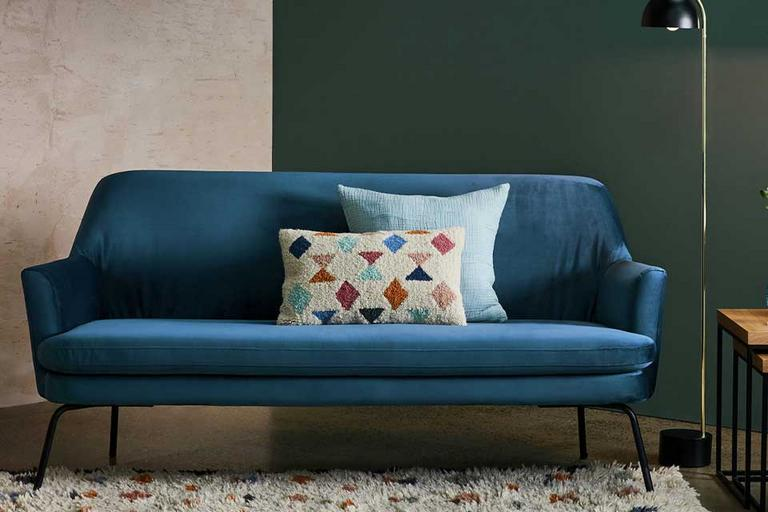 A blue Scandi-styled sofa in a lounge with a geometric rug in front.