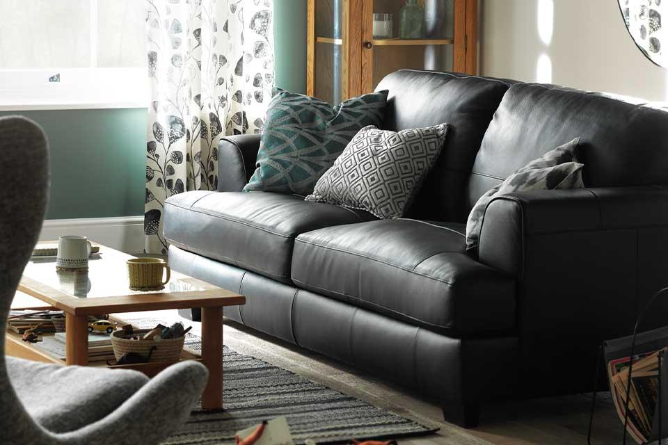 A black leather sofa in a cosy lounge setting.