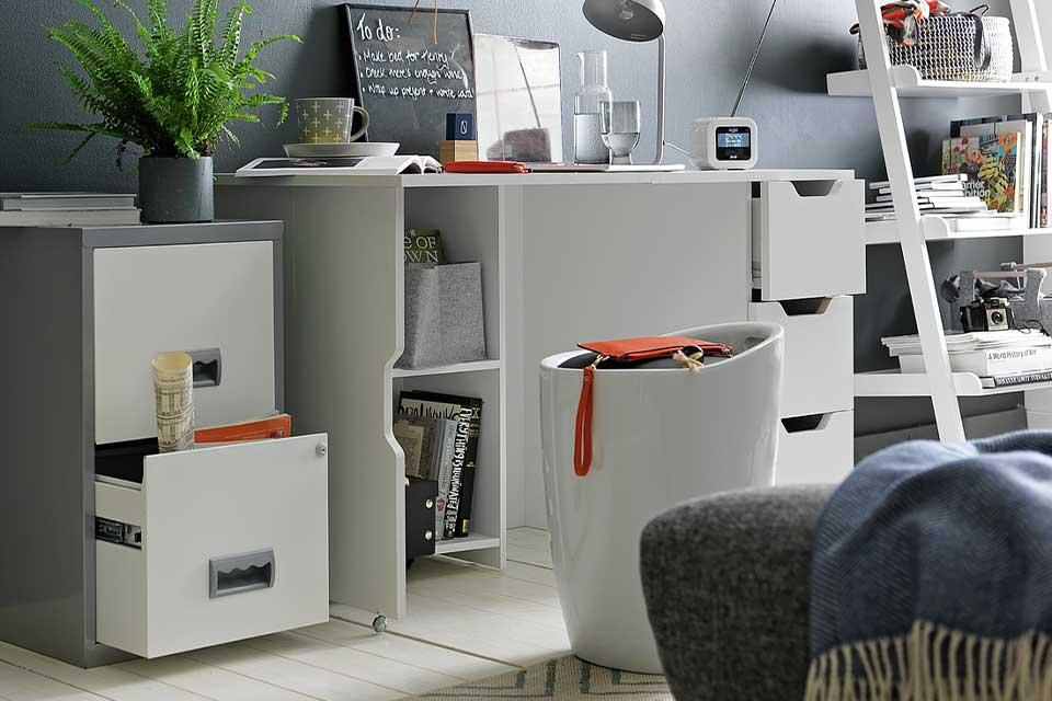 A home office with a filing cabinet, desk and ladder shelves.