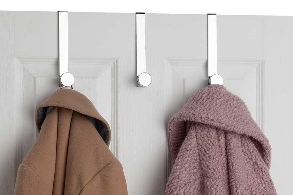 Three over the door stainless steel hooks with coats hanging from them.