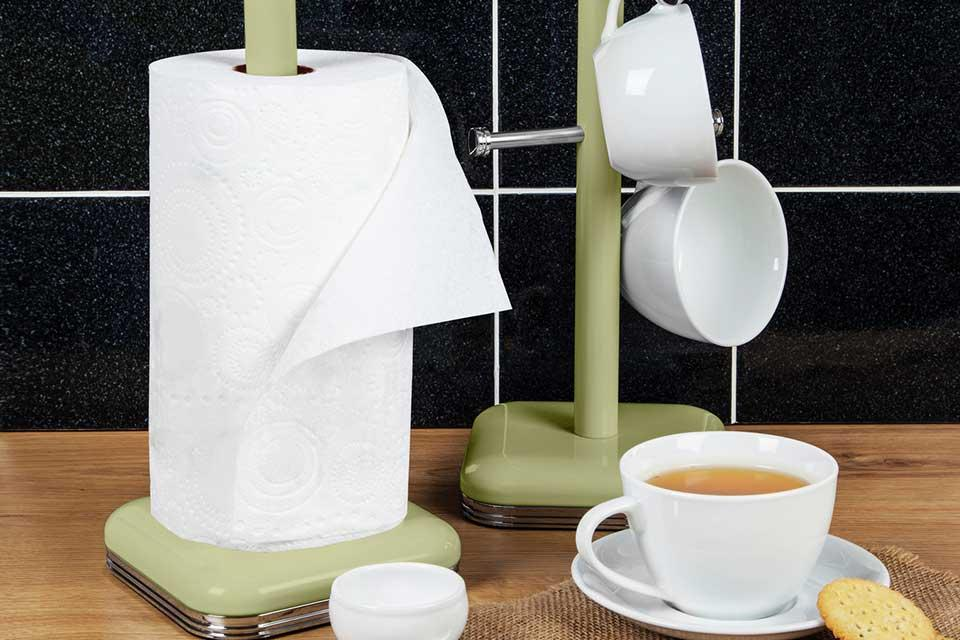 A green kitchen roll holder and tree mug with a cup of tea in front.