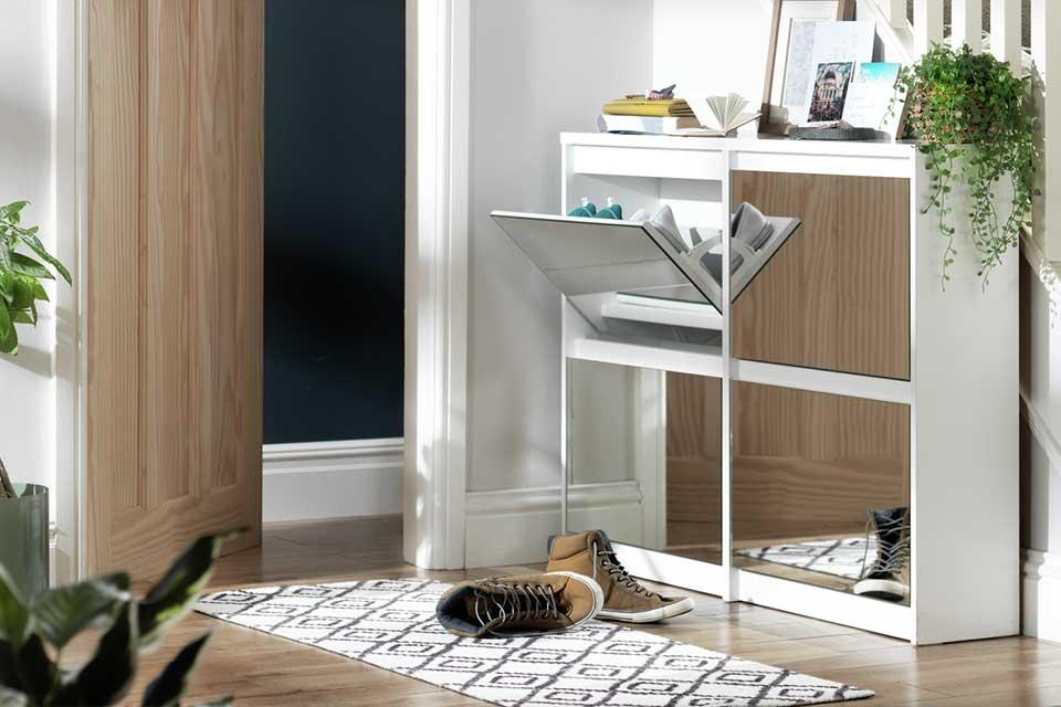 A hallway with the Habitat Jenson mirrored shoe cabinet with boots in front of it.