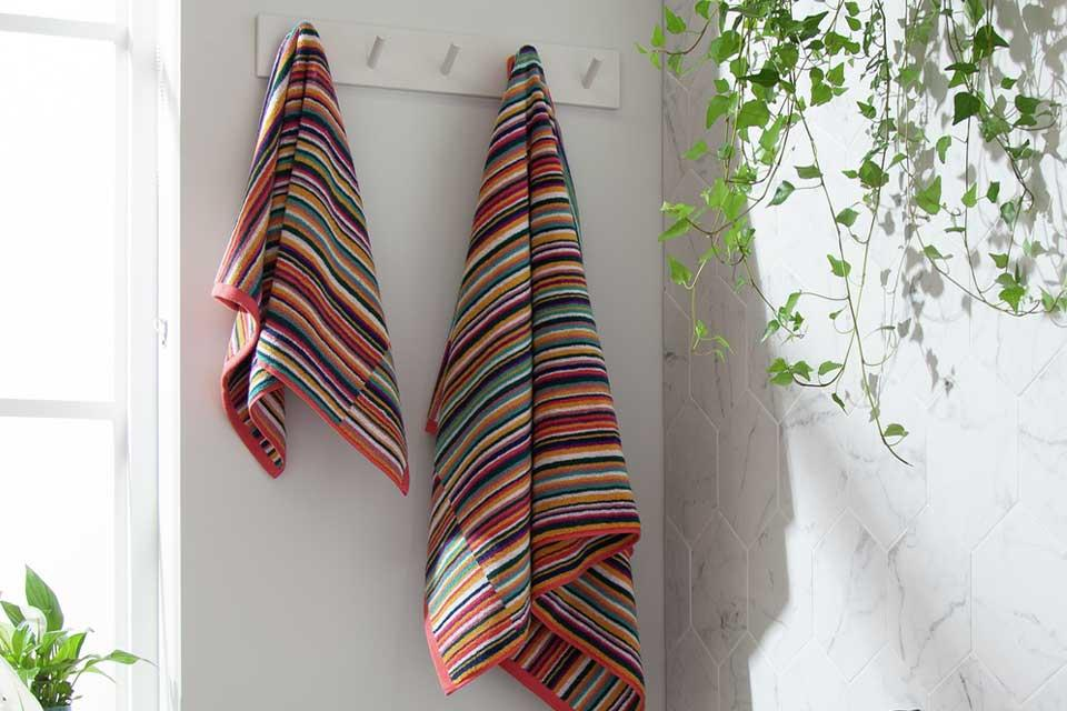 Two stripey colourful towels hanging up on hooks in a bathroom.