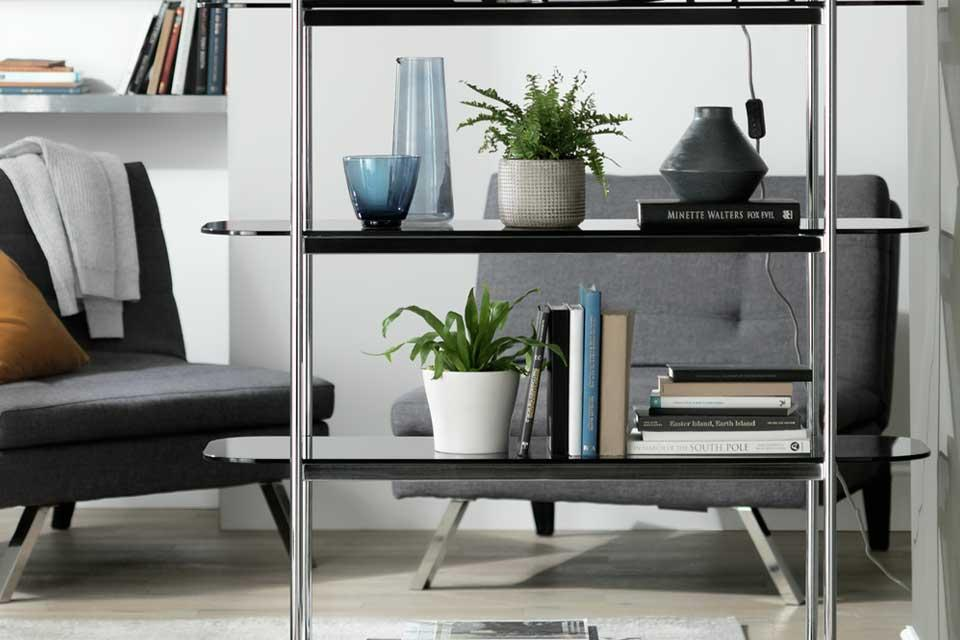 The Habitat Neo 5 tier shelving unit in chrome in a lounge setting.