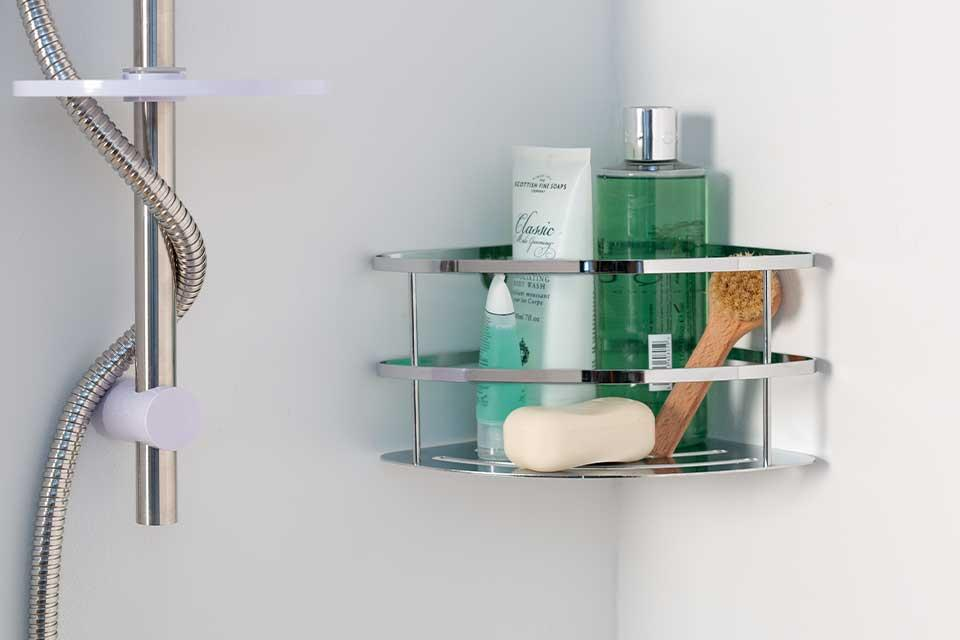 Argos Home wall-mountable corner shelf in chrome with bathroom bits inside.
