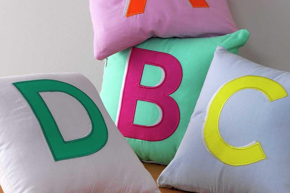 Colourful letter cushions A-D in pink, green and blue.
