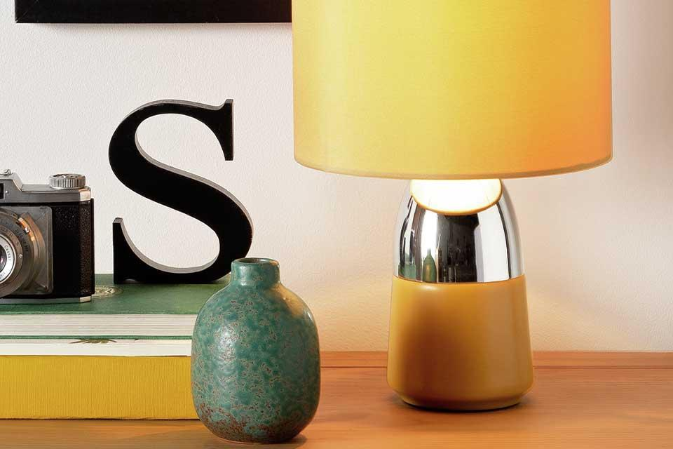 Mustard and chrome touch table lamp next to a green ornament.