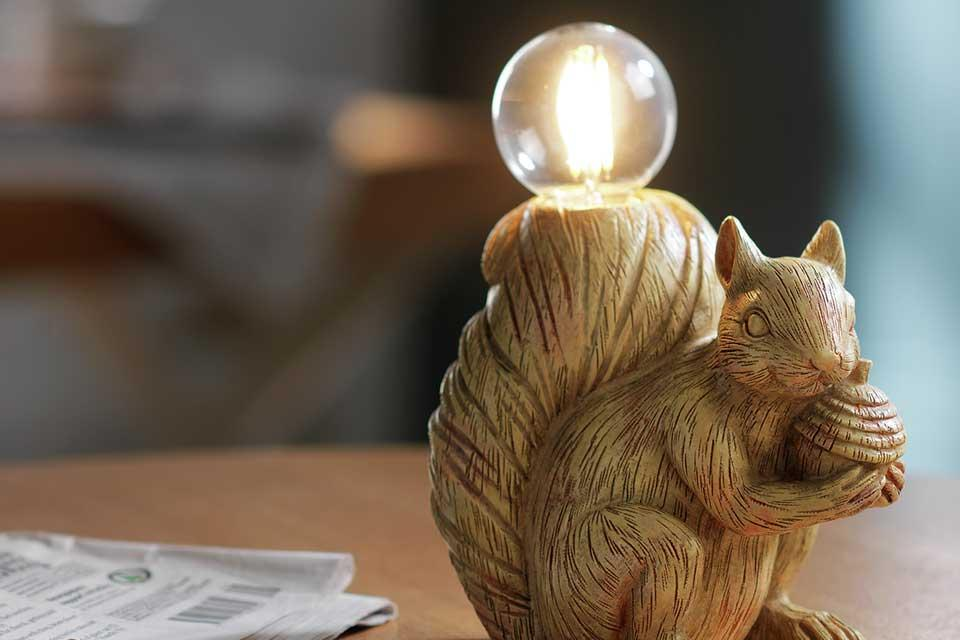 Cyril the squirrel lamp with exposed bulb in his tail, sitting on a desk.