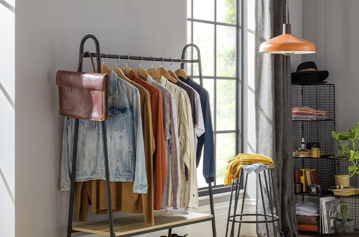 A grey hanging clothes rail in a bright, open bedroom.
