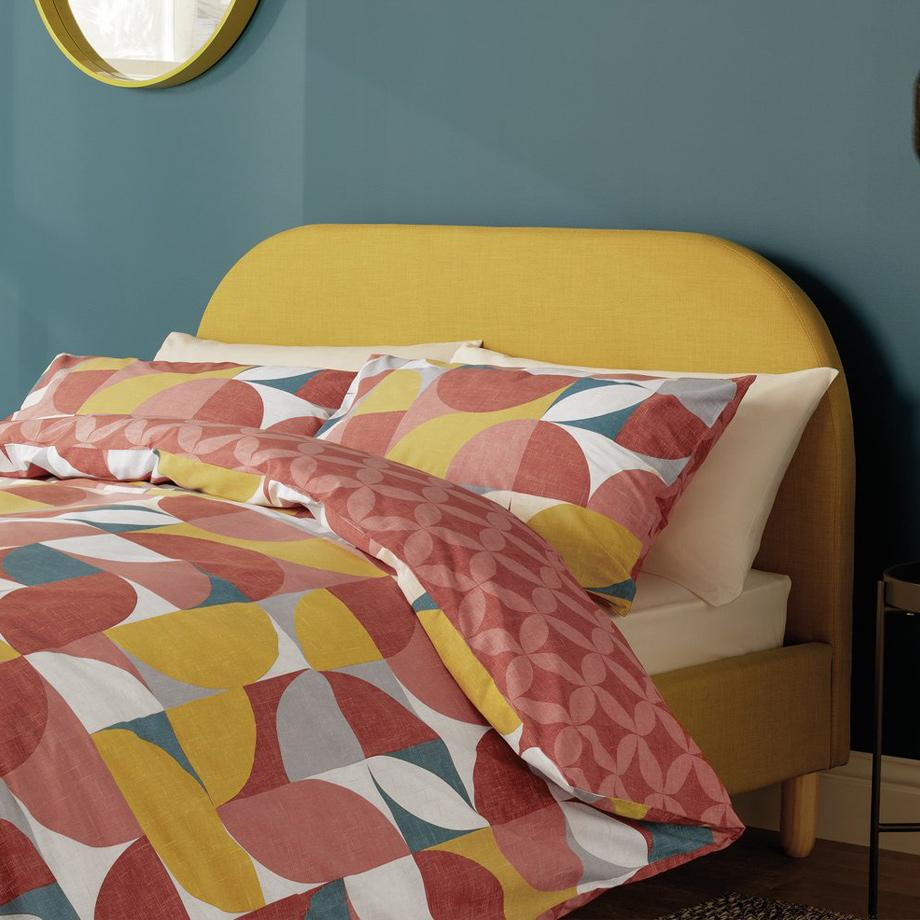 Bright, geometic duvet set on a mustard yellow bed.