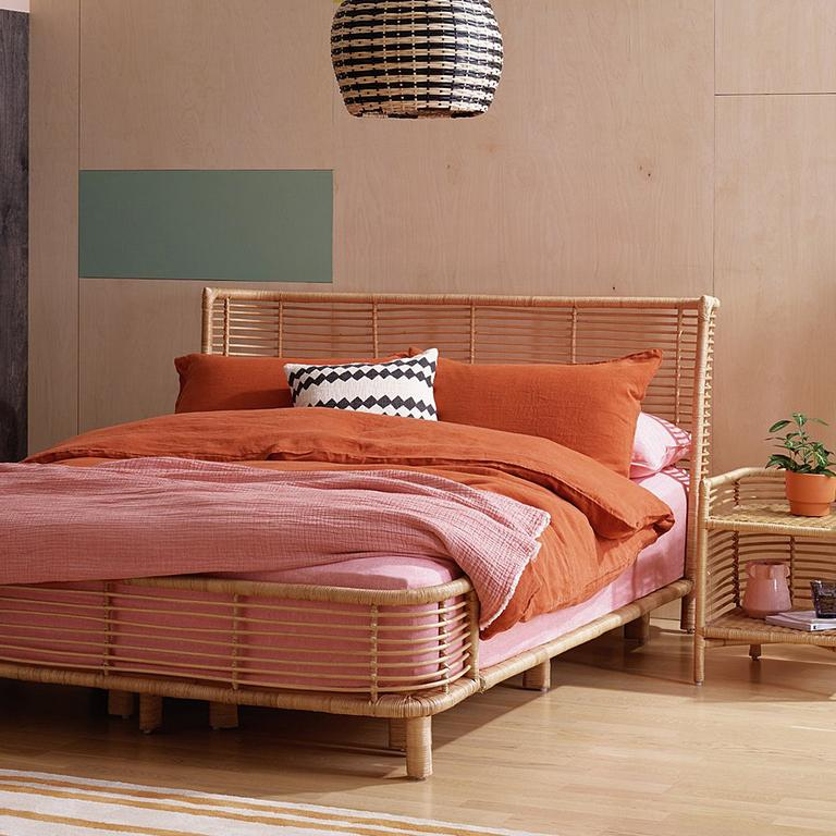 Terracotta duvet set on a rattan bed, in a bedroom decorated with earthy tones.