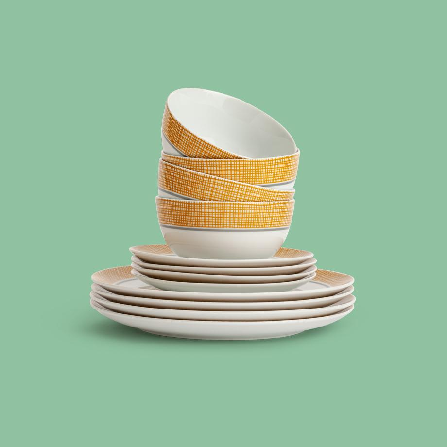 A white and yellow stack of bowls, side plates and dinner plates.