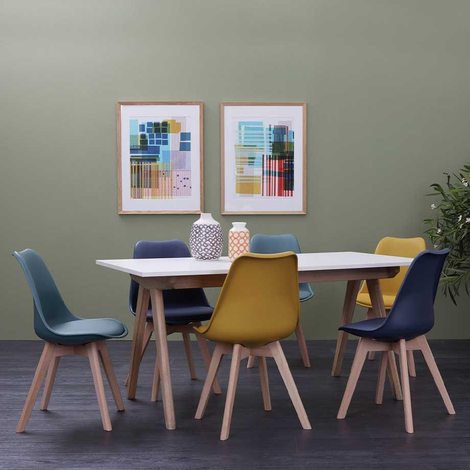 Scandi-styled table with Habitat Jerry chairs in mustard, blue and green with splayed legs.