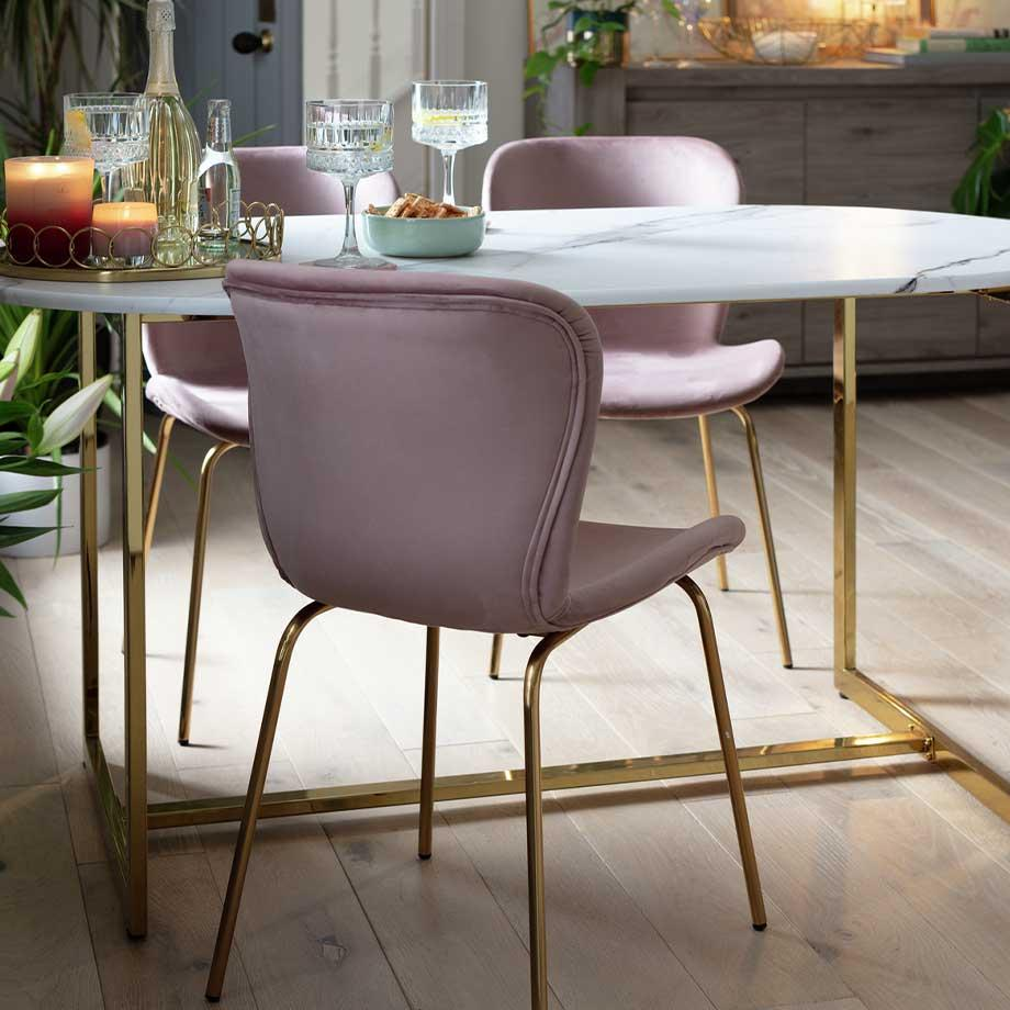 The Habitat Vivien marble-effect dining table with gold-effect legs and pink dining chairs.