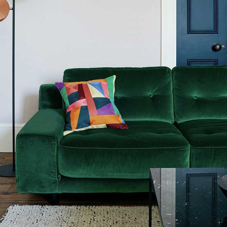 The green Habitat Hendricks sofa with a colourful scatter cushion and button back.