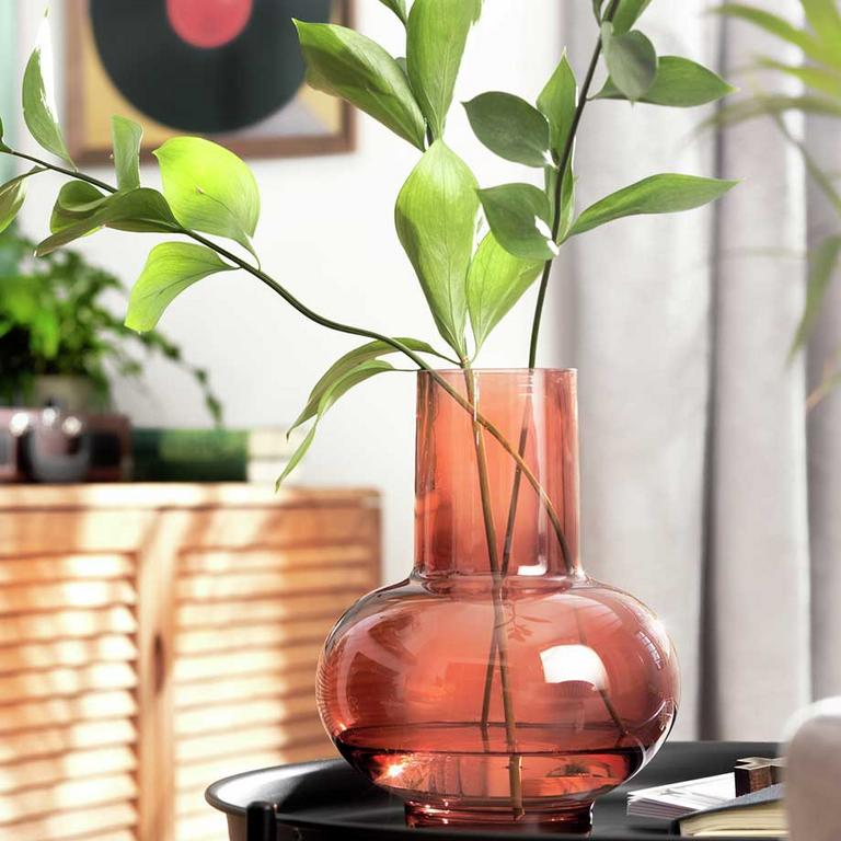 A Habitat orange mid-century vase with a green plant in.
