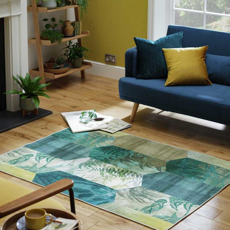 The Argos Home Eden leag tile rug in front of a blue sofa.