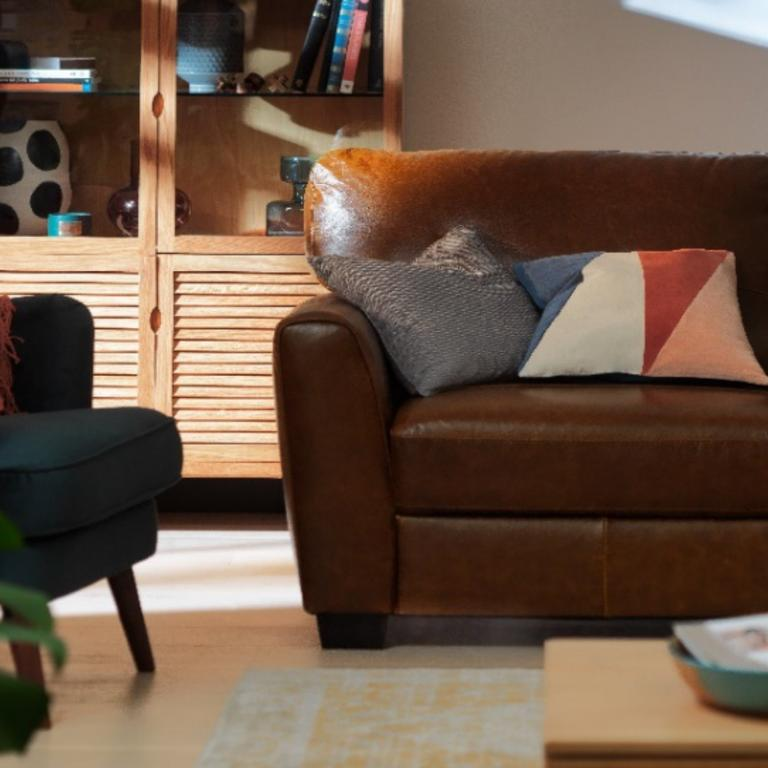 A brown leather armchair with fun, mismatched cushions.