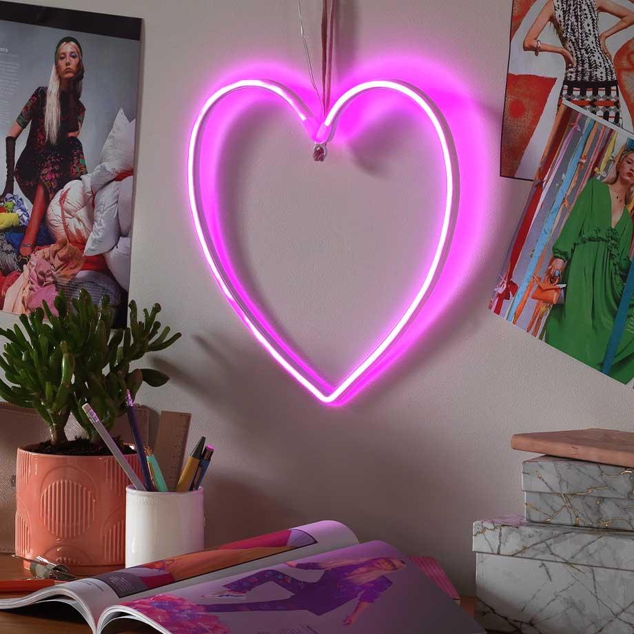 A heart neon light in a teen bedroom above a desk with magazines.