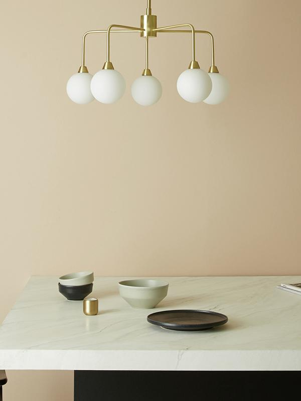 A white and gold claw style ceiling light against a peach coloured wall.