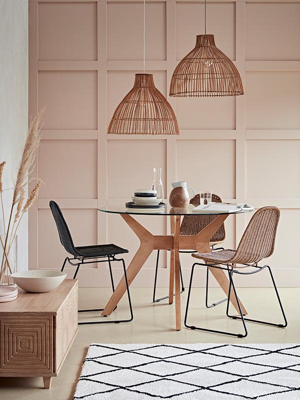 A round glass and wood dining table with rattan chairs and accents.