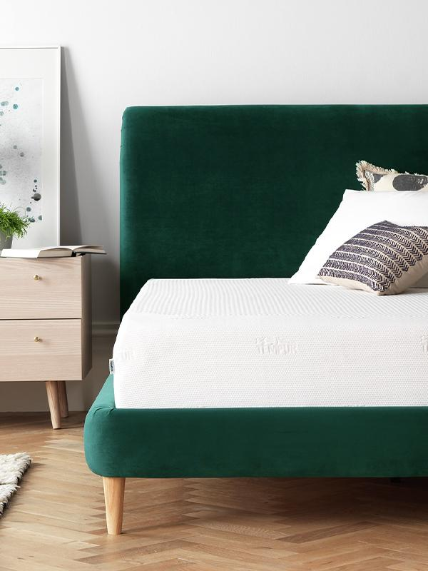 A green velvet bed and white mattress.