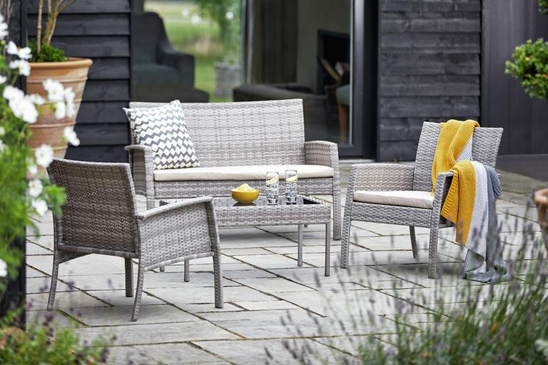 A grey garden furniture set on a patio.