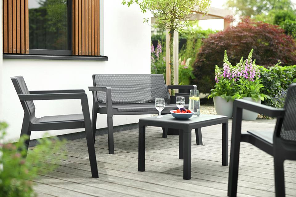 A plastic sofa, chairs and table garden furniture set.