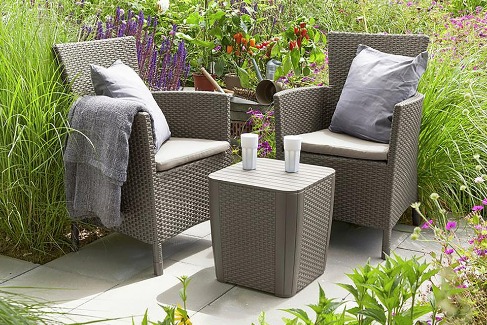 Two rattan effect grey garden armchairs, with a grey rattan effect table.