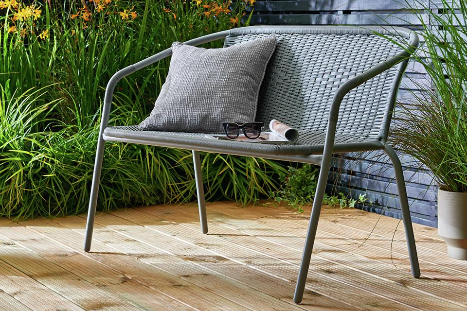 Grey ratan and metal bench, with a grey cushion.