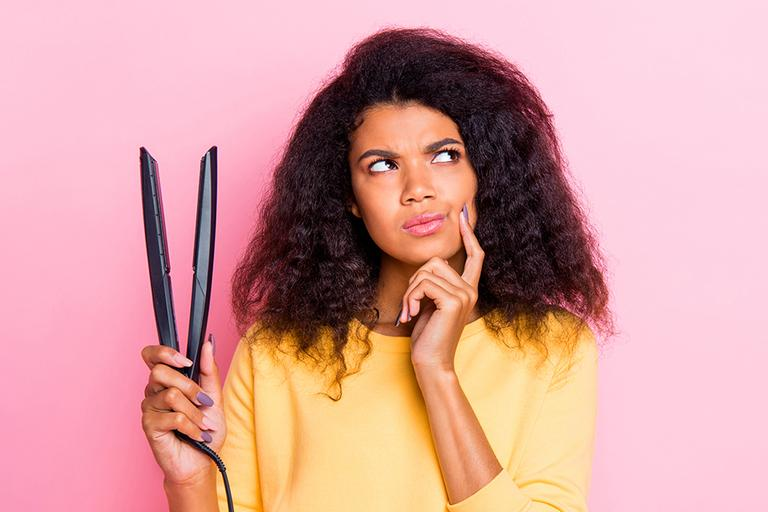 A woman holding a set of hair straighteners.
