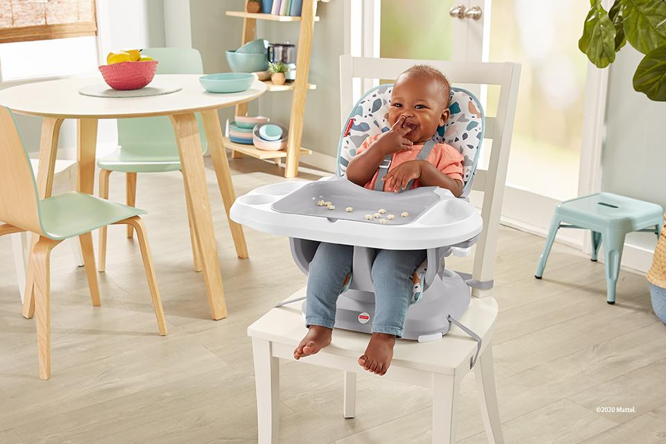Baby sitting in space saver fisher-price high chair eating.