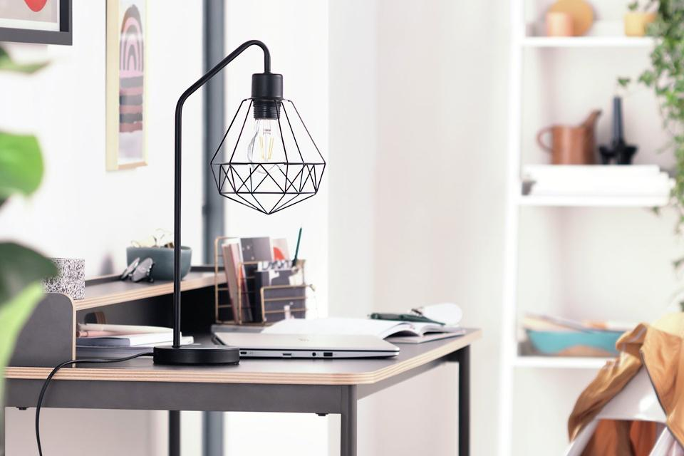 A black diamond cage table lamp on a desk.