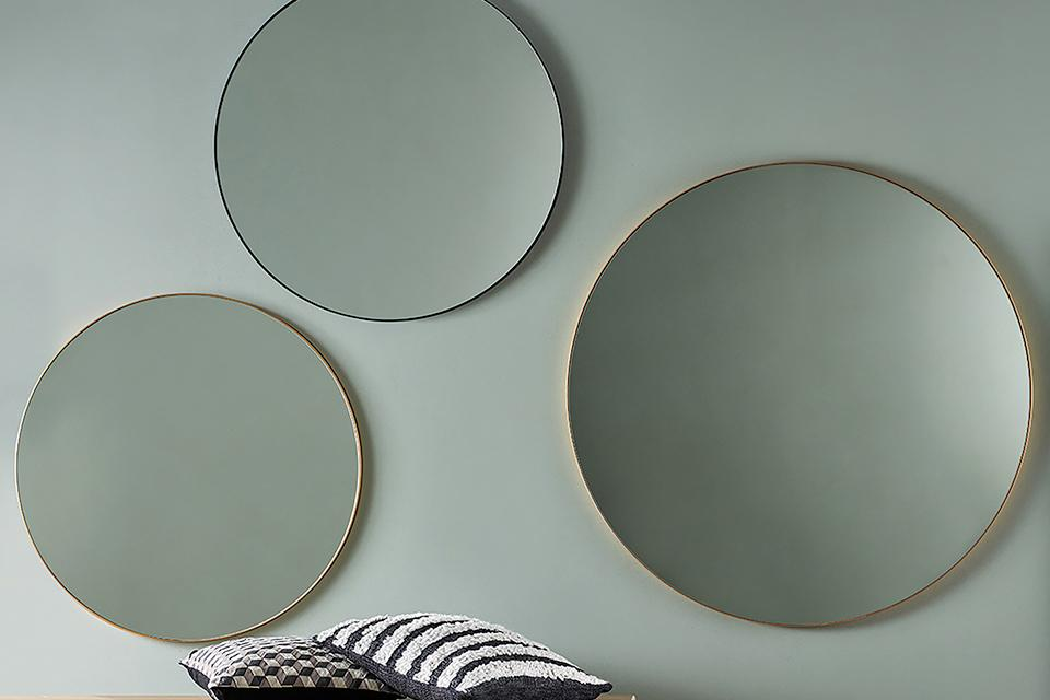 Three round mirrors hanging on the wall in brass and black.