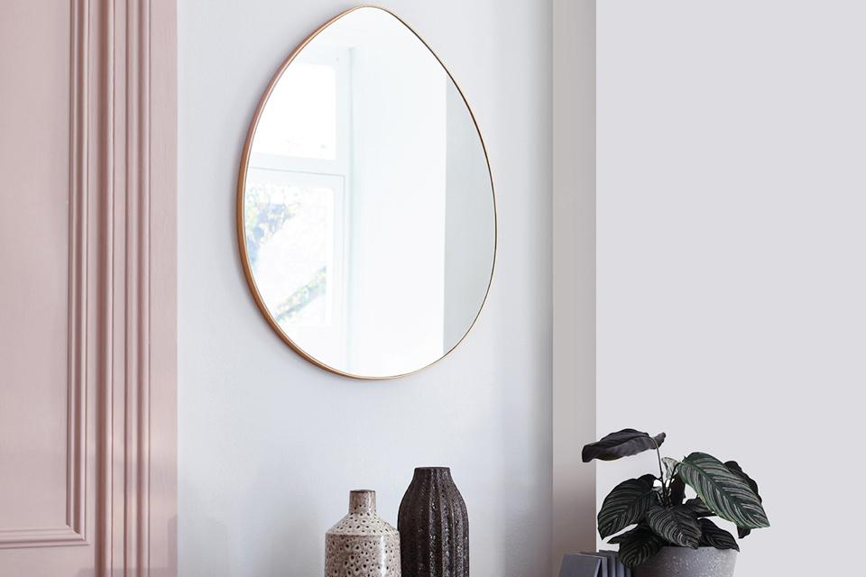 A gold teardrop mirror hanging on the wall.